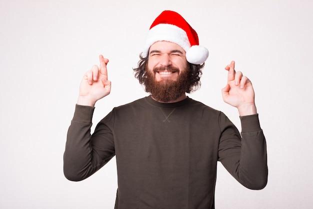 Knappe bebaarde man die een wens doet en vingers kruist en kerstman hoed draagt