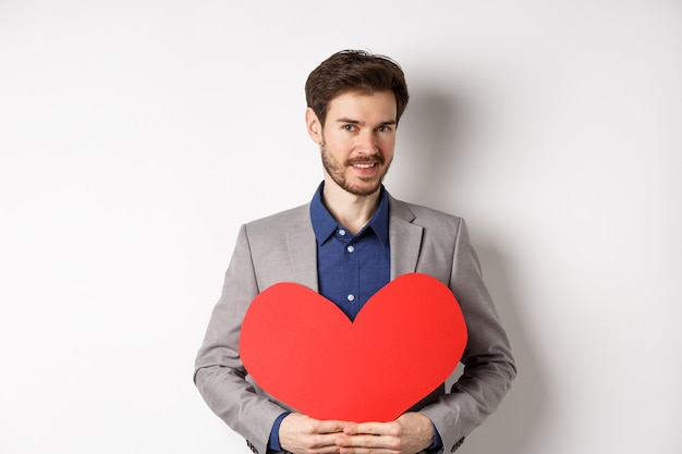 Knappe bebaarde man die gelukkige valentijnsdag wenst, rood hart knipsel houdt en lacht, romantische date in chique pak gaande is, staande op een witte achtergrond.