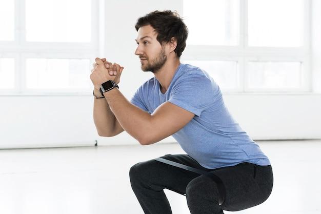Knappe bebaarde man doet squats met een lusweerstandsband tijdens training in de sportschool