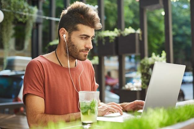 Knappe bebaarde man, freelancer werkt op afstand van terras, programmeur met laptop luisteren muziek om zich op het werk te concentreren