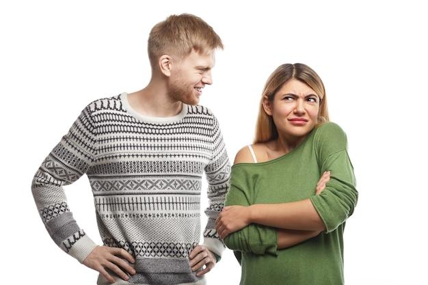 Knappe bebaarde man gekleed in trui glimlachend en kijkend naar aantrekkelijke vrouw die in gesloten houding met gekruiste armen staat, zich verward voelt omdat ze zijn domme grap niet leuk vindt of begrijpt