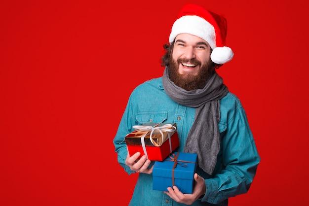 Knappe bebaarde man geschenkdozen houden op rode achtergrond en kijken gelukkig camera