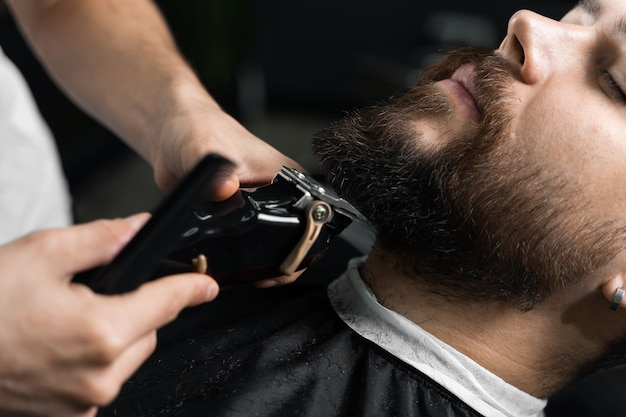 Knappe bebaarde man heeft haar en baard geknipt in de kapperszaak. dreadlock-kapper knipt het haar van de klant.