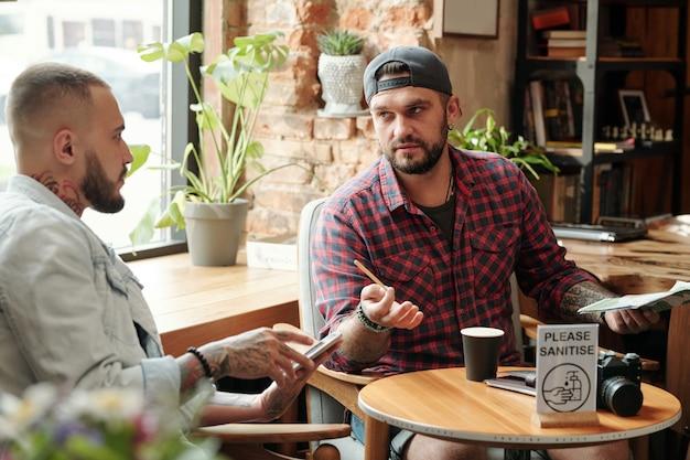 Knappe bebaarde man in bal glb en casual shirt zittend aan tafel in moderne café en koffie drinken met vriend terwijl ze werk bespreken