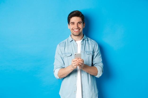 Knappe bebaarde man in casual outfit glimlachend in de camera, smartphone controlerend, staande tegen blauwe achtergrond