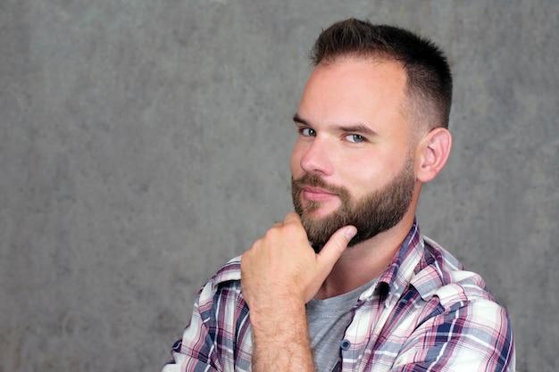 Knappe bebaarde man in een shirt, kijkt met intriges en interesse in de camera op grijs