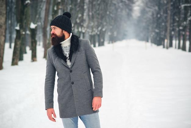 Knappe bebaarde man in jas en hoed in de winter