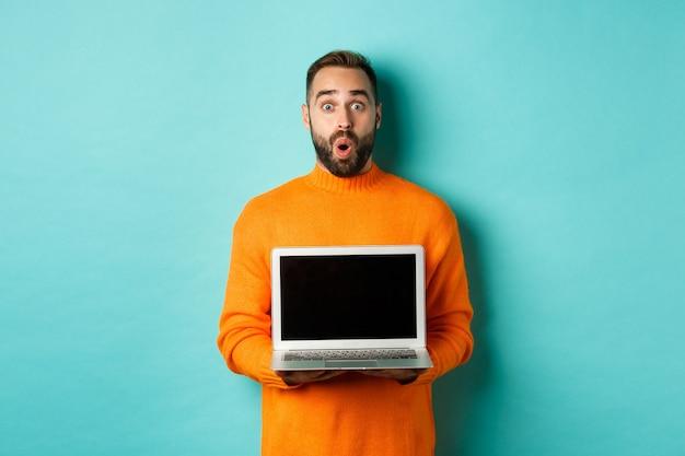 Knappe bebaarde man in oranje trui met laptopscherm, demonstrerende promo, staande over lichtblauwe achtergrond