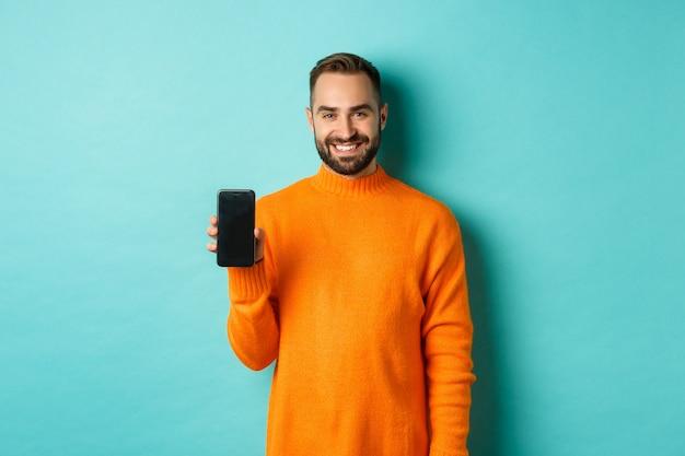 Knappe bebaarde man in oranje trui, smartphonescherm tonen en glimlachen, promo online, turquoise muur tonen.