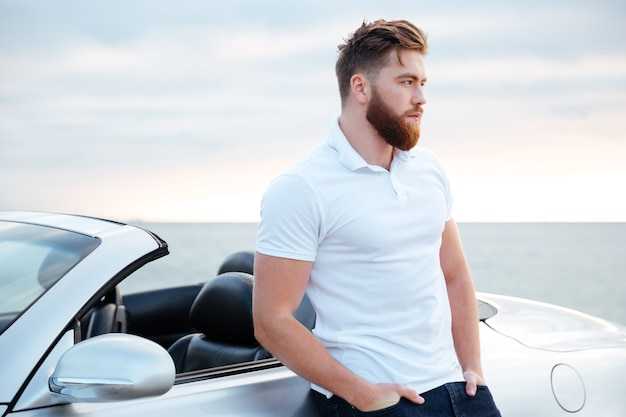 Knappe bebaarde man in wit overhemd leunend op auto terwijl je op het strand