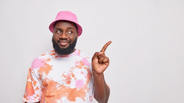Knappe bebaarde man met dikke baard donkere huid wijst weg op kopieerruimte toont advertentie draagt roze panama en verwassen t-shirt beveelt product aan toont logo