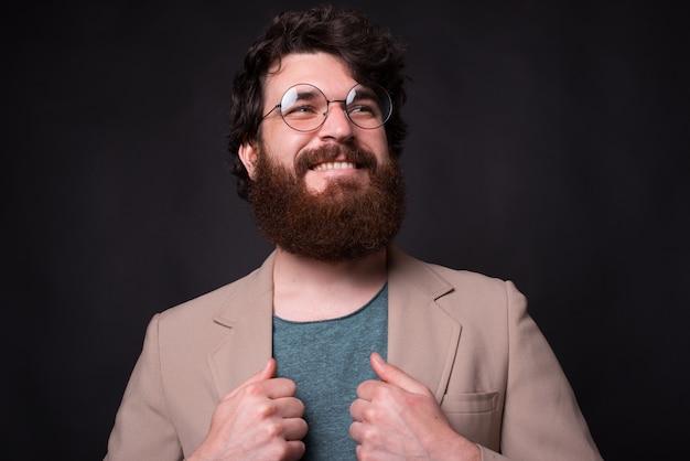 Knappe bebaarde man met een bril lacht, kijkt omhoog, houdt zijn jas vast.