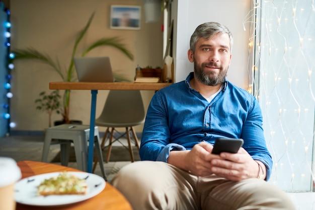 Knappe bebaarde man met grijze haren zitten door raam in café en camera kijken terwijl scrollen in smartphone