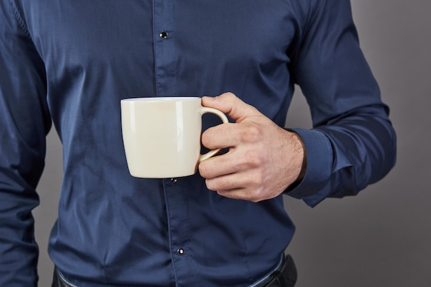 Knappe bebaarde man met stijlvolle haar baard en snor op ernstig gezicht in shirt met witte kop of mok thee of koffie drinken in de studio op grijs