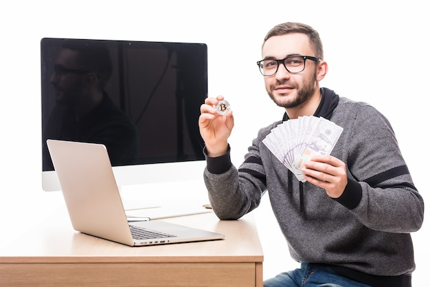 Knappe bebaarde man op zijn werkplek met laptop en pc-beeldscherm achterop met bitcoin en dollars contant in handen