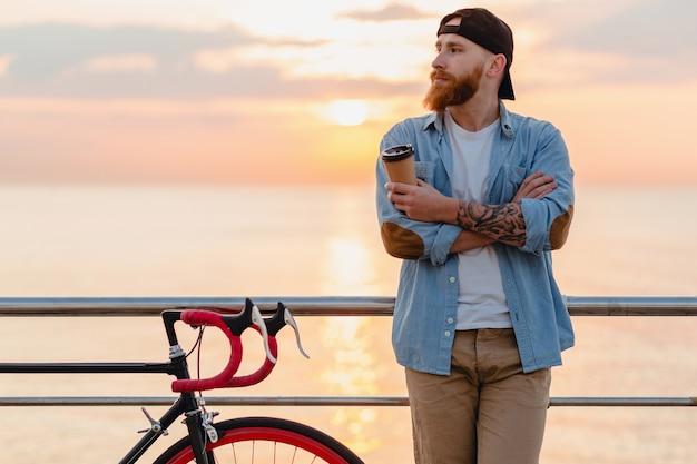 Knappe bebaarde man reizen met de fiets in de ochtend zonsopgang door de zee koffie drinken, gezonde actieve levensstijl reiziger