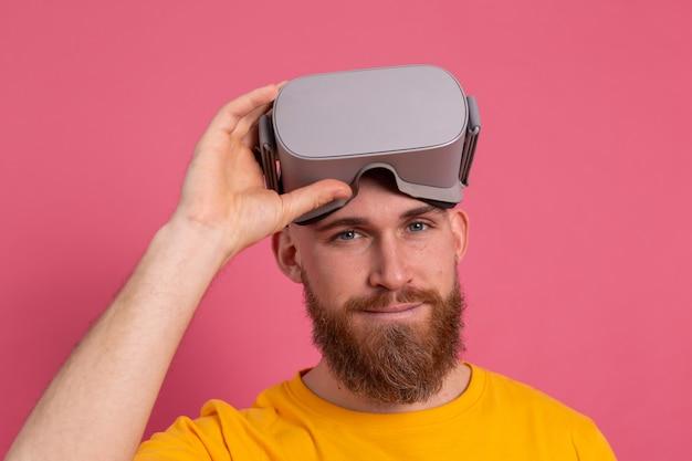 Knappe bebaarde man stijgt vr-bril studio achtergrond