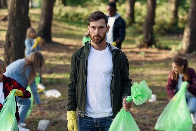 Knappe bebaarde man toont een vol vuilnisbak op de achtergrond van vrijwilligers van zijn vrienden die afval ophalen in het park.