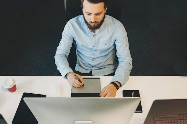 Knappe bebaarde man zittend aan tafel in kantoor en puttend uit moderne grafisch tablet