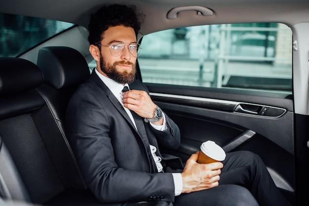 Knappe bebaarde manager zit met koffie to go op de achterbank van de nieuwe auto
