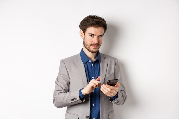 Knappe bebaarde mannelijk model in pak met behulp van mobiele telefoon, glimlachend tevreden op camera, witte achtergrond.