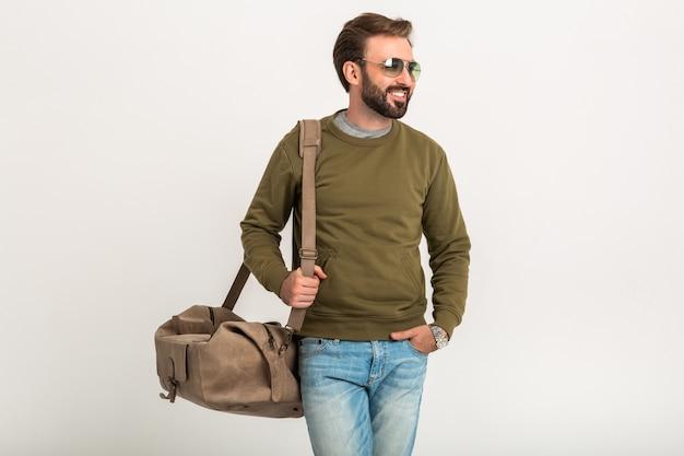Knappe bebaarde stijlvolle man poseren geïsoleerd gekleed in sweatshirt met reistas, spijkerbroek en zonnebril dragen