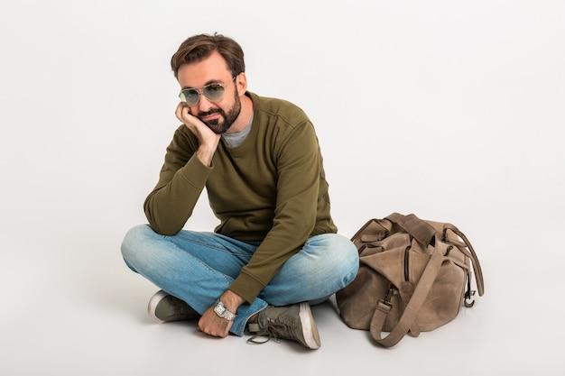 Knappe bebaarde stijlvolle man zittend op de vloer geïsoleerd gekleed in sweatshirt met reistas, spijkerbroek en zonnebril, verdrietig en moe wachten