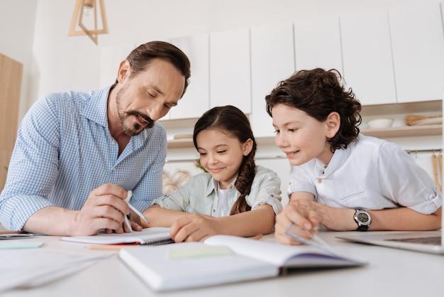 Knappe bebaarde vader die zijn kinderen helpt bij het maken van wiskundeopdrachten door een cirkel met een kompas in te schrijven