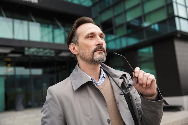 Knappe bebaarde zakenman die een bril vasthoudt en vooruitkijkt in de buurt van een kantoorgebouw in stedelijk gebied