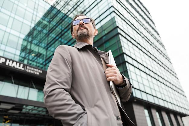 Knappe bebaarde zakenman in bril met laptop terwijl hij in de buurt van kantoorgebouw in stedelijk gebied staat