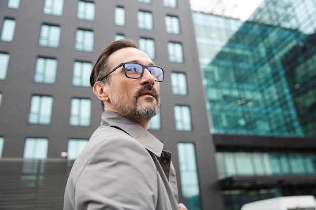 Knappe bebaarde zakenman in bril poseren en kijken uit in de buurt van kantoorgebouw in stedelijk gebied