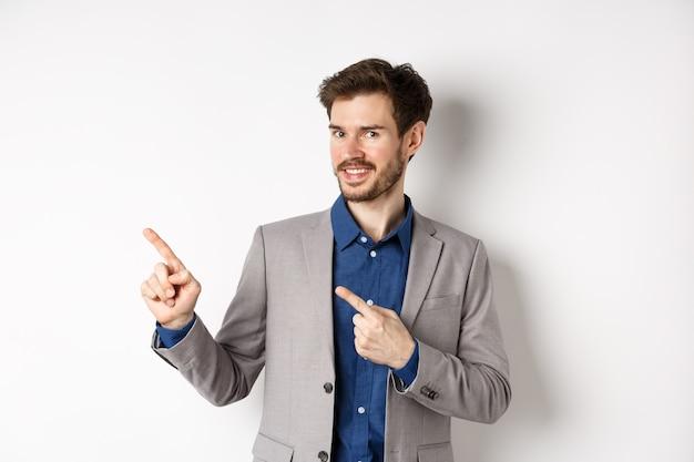 Knappe bebaarde zakenman in grijs pak wijzende vingers links op logo, check-out advertentie uitnodigend, staande op een witte achtergrond.