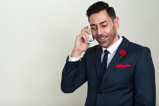 Knappe bebaarde zakenman pak dragen tegen witte ruimte