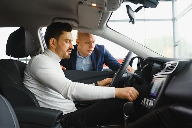 Knappe bebaarde zakenman zit in een nieuwe auto in autodealer