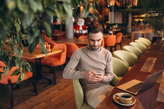 Knappe bedrijfsmens die aan computer en het drinken koffie in een koffie werkt