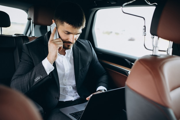 Knappe bedrijfsmens die aan een computer in auto werkt