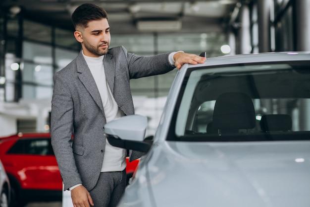 Knappe bedrijfsmens die een auto in een autoshowroom kiest