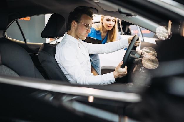 Knappe bedrijfsmens die een auto in een autotoonzaal kiest