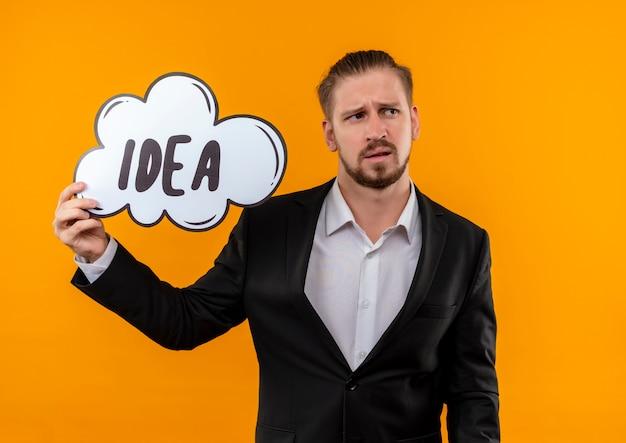 Knappe bedrijfsmens die het woordidee van de kostuumholding in een toespraakbel draagt die opzij verbaasd status over oranje achtergrond kijkt