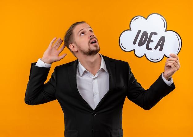 Knappe bedrijfsmens die het woordidee van de kostuumholding in een toespraakbel dragen die omhoog verward status over oranje achtergrond opzoeken