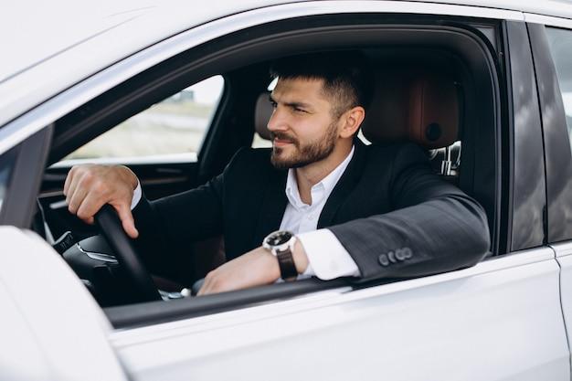 Knappe bedrijfsmens die in een auto reist