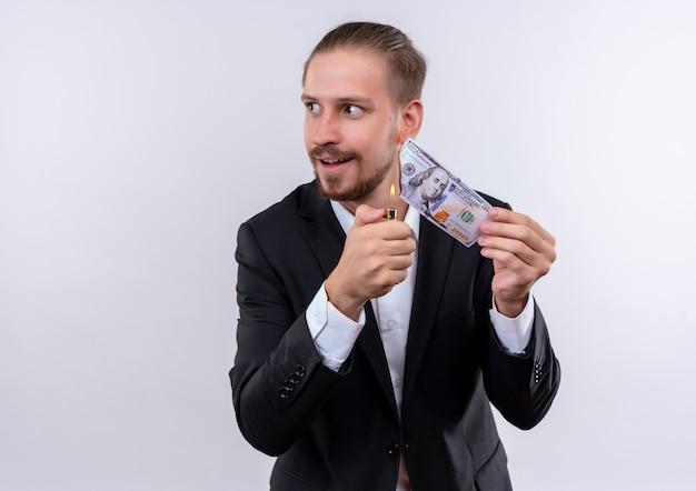 Knappe bedrijfsmens die kostuum brandend geld draagt dat opzij kijkt met sluwe glimlach die zich over witte achtergrond bevindt