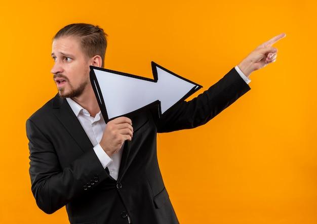 Knappe bedrijfsmens die kostuum draagt dat witte pijl houdt die met vinger aan de kant kijkt die verward zich over oranje achtergrond bevindt