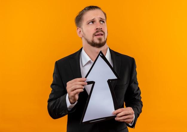 Knappe bedrijfsmens die kostuum draagt dat witte pijl houdt die omhoog verward status over oranje achtergrond kijkt