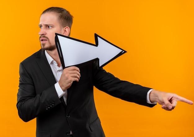 Knappe bedrijfsmens die kostuum draagt dat witte pijl met vinger naar de kant houdt die verward kijkt die zich over oranje achtergrond bevindt