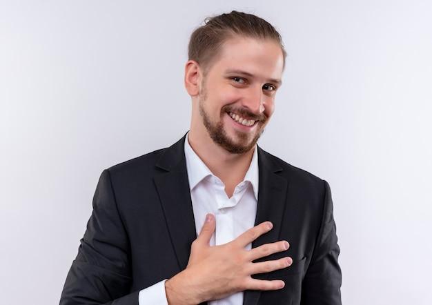 Knappe bedrijfsmens die kostuum draagt die hand op zijn borst houdt die camera met glimlach op gezicht bekijkt die zich over witte achtergrond bevindt