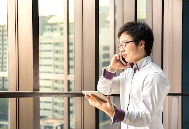 Knappe bedrijfsmens die met tablet en slimme telefoon in bureau werkt
