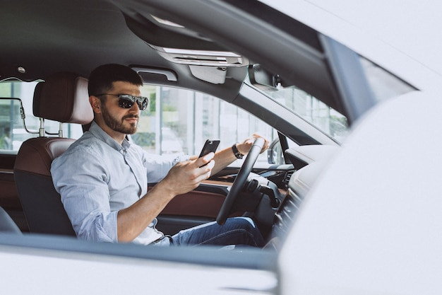 Knappe bedrijfsmens die telefoon in auto met behulp van
