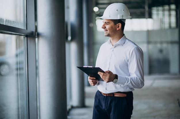Knappe bedrijfsmenseningenieur in bouwvakker in een gebouw