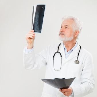 Knappe bejaarde arts met röntgenfoto